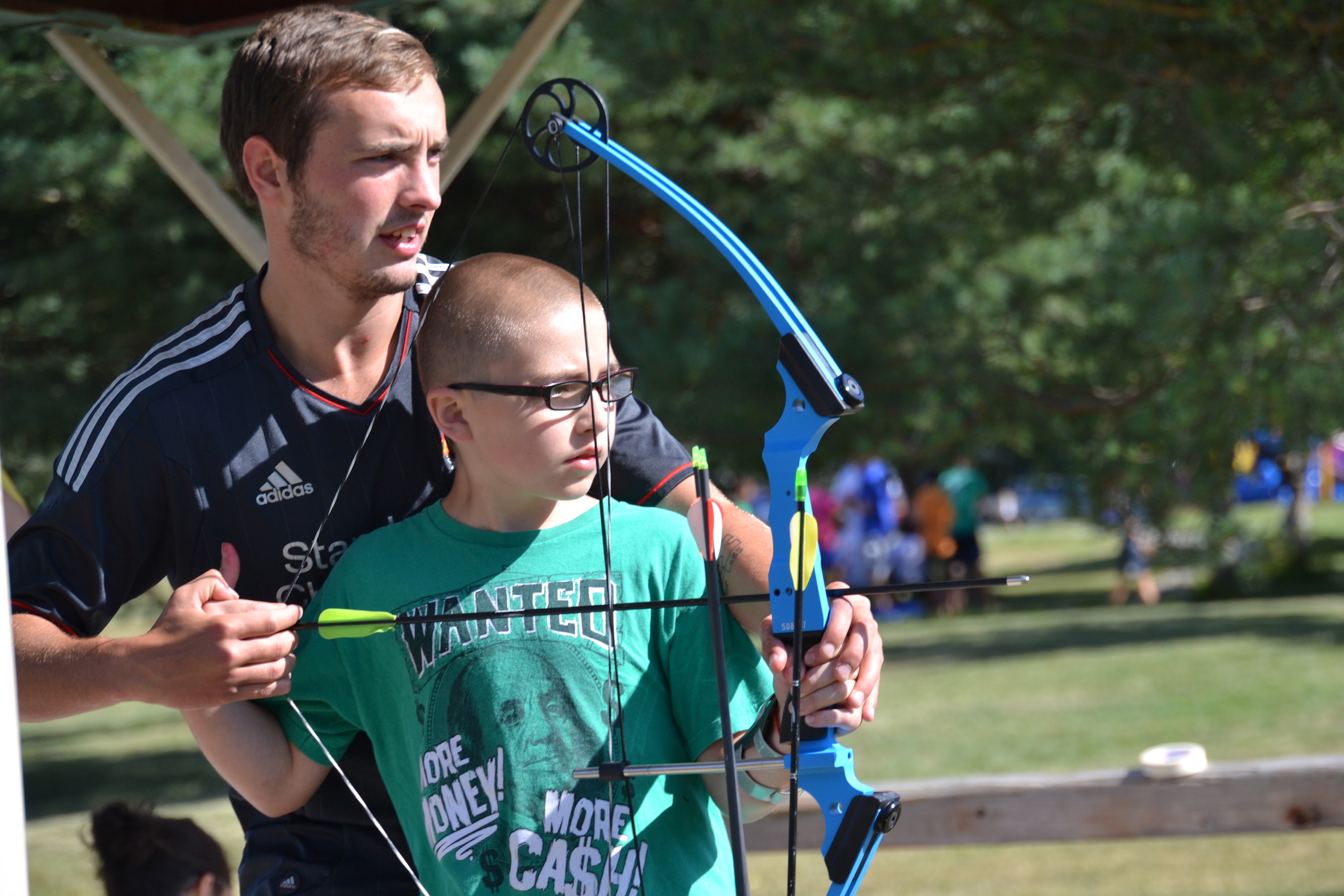 Special needs child doing archery at Easter Seals summer camp